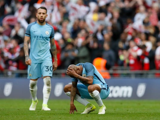Manchester City's Fabian Delph and Nicolas Otamendi, left, react at the end of the English FA Cup semifinal soccer match between Arsenal and Manchester City at Wembley stadium in London, Sunday, April 23, 2017. Arsenal won 2-1. (AP Photo/Kirsty Wigglesworth)