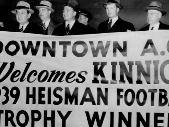 Nile Kinnick, third from right, stands behind a welcome sign waiting for him at Floyd Bennett airport when he arrived Dec. 7, 1939 in New York for the Heisman Trophy ceremony. Second from right is Iowa coach Eddie Anderson.