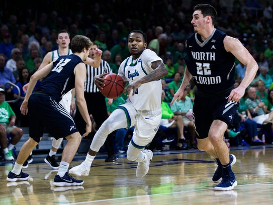 Florida Gulf Coast University guard Brandon Goodwin (0) carries the ball between two defenders during the ASUN tournament semifinal game against North Florida at Alico Arena on Thursday.