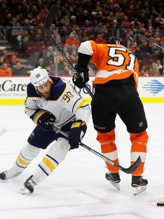 Buffalo Sabres' Ryan O'Reilly, left, goes around Philadelphia Flyers' Valtteri Filppula, right, of Finland, to get the puck after the face-off during the first period of an NHL hockey game, Thursday, Dec. 14, 2017, in Philadelphia. (AP Photo/Chris Szagola)