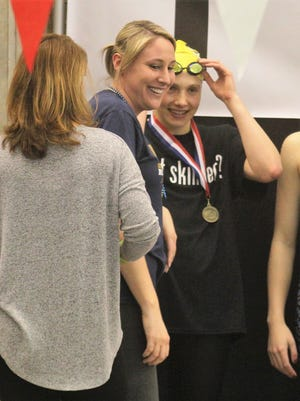 Notre Dame head coach joins senior Sophie Skinner after Skinner's medal ceremony in her 100 free championship during the KHSAA state swimming and diving championships Feb. 24, 2018 at the University of Louisville.