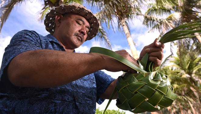 Chamorro teacher and weaver Joe Dågu Babauta displays weaves a tasa, or upper part of a Chamorro latte stone, with leaves of the niyok, or coconut, tree while at the War in the Pacific National Historical Park's Asan Beach Unit on Wednesday, July 19, 2017.