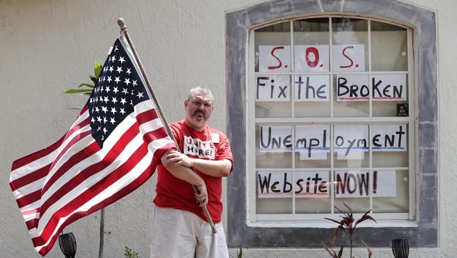 Hew Kowalewski, a furloughed employee of Disney World stands next to a window of his home Monday in Kissimmee. Many of Florida's jobless have reported problems filing applications for unemployment benefits. [JOHN RAOUX/THE ASSOCIATED PRESS] =