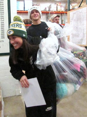 Smiling Arctic League volunteers prepare to hit the streets Dec. 25, 2015, with bags of gifts for needy children and families.