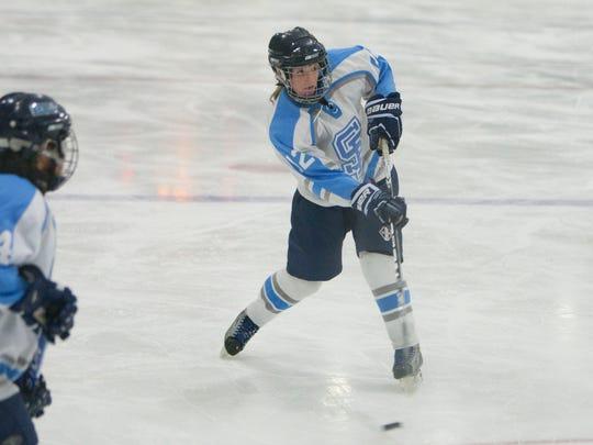 Sarah Fisher (12) of South Burlington rips a shot during a high school girls hockey game.