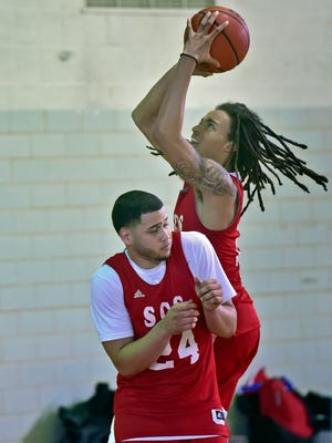 Koreem Ozier, right, shoots over teammate Kevin Fernandez during Scotland Campus Sports basketball team. practice. The players were photographed on Wednesday, December 6, 2017.
