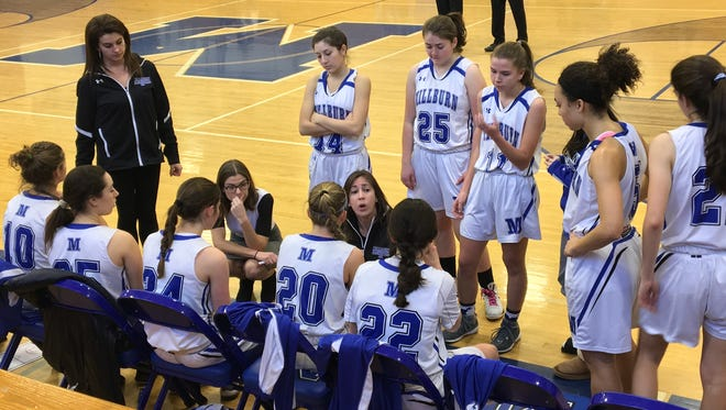 Millburn head coach Stacy Dinner (center) talks to her team in a timeout.