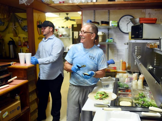 Steve Horn (right) shares a laugh with a customer while preparing lunch as Will Watkins delivers drinks on Monday, April 9, 2018 at The Barefoot Cafe in downtown Vero Beach. Horn and his wife Lisa opened the cafe in 2007 specializing in wraps, salads and soup. The Horns have decided to sell the business to Watkins, sell off most of their possessions and travel the country.