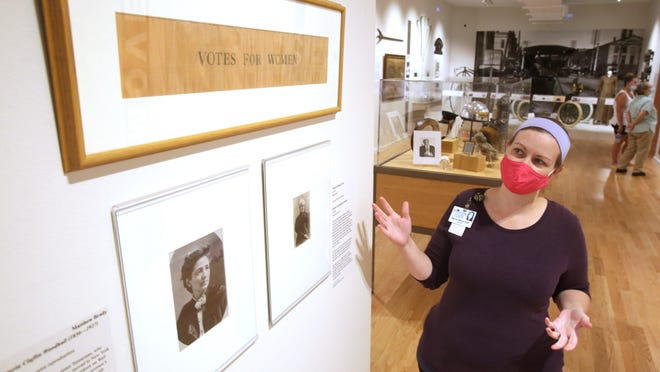 Mandy Altimus Stahl, archivist at the Massillon Museum, talks about some of the women's suffrage movement pieces on display in the museum's permanent gallery. One iconic piece is a sash from the movement that was worn in Massillon. Photographs of Victoria Claflin Woodhull (left) and Caroline McCullough Everhard, prominent women working to get women the right to vote also are also pictured.