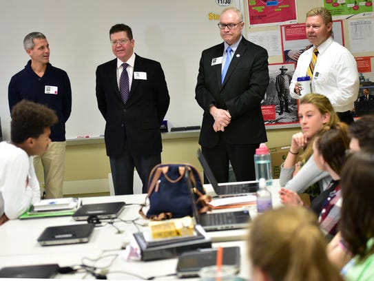 Government officials chat with students in teacher