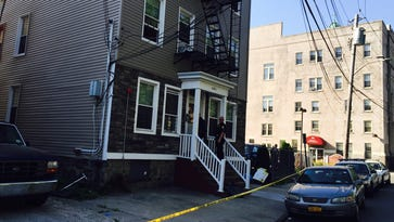 Yonkers police officers enter an apartment building May 26, 2015, where a 4-year-old girl shot herself in the face the night before.