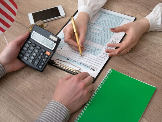 business woman is reviewing 1040 tax form with taxconsultant