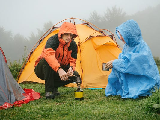Tourists cooking coffee near tent in the mountains