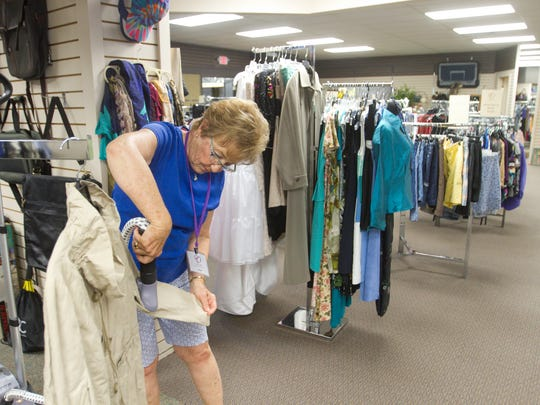 Nancy Lawton steams a jacket Tuesday, June 20, 2017 which was donated to Love INC's resale store on Grand River Ave. in Howell.