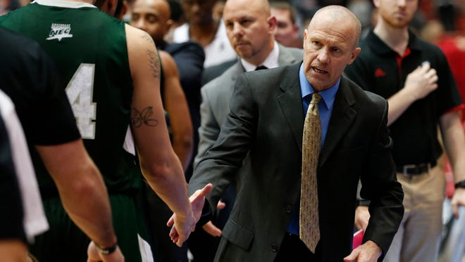 UC's Larry Davis shakes hands with players after the Bearcats' game against Wagner on Dec. 23.