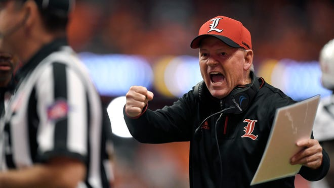 Louisville head coach Bobby Petrino tries to get the referees attention during the first half of an NCAA college football game against Syracuse in Syracuse, N.Y., Friday, Nov. 9, 2018. (AP Photo/Adrian Kraus)