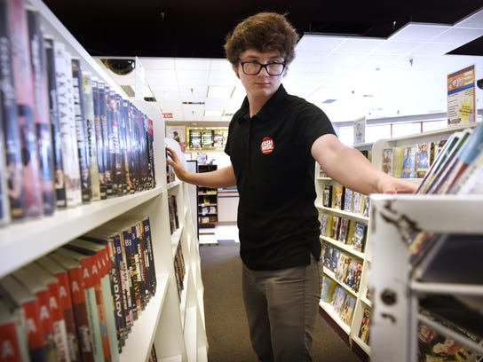 Eric Macaw puts DVDs on a shelf on July 15 at Cash