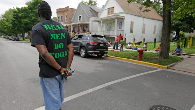 """Andres Brown, a member of a non-profit group called """"I Grow Chicago,"""" patrols an intersection June 24 where an IGC yoga class is taking place on the often violent streets of Chicago's Englewood neighborhood."""