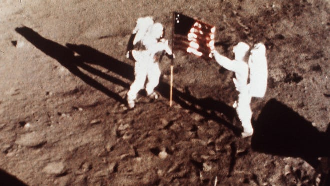 "FILE - In this July 20, 1969 file photo, Apollo 11 astronauts Neil Armstrong and Edwin E. ""Buzz"" Aldrin, the first men to land on the moon, plant the U.S. flag on the lunar surface.  Photo was made by a 16mm movie camera inside the lunar module, shooting at one frame per second.  (AP Photo/NASA, file) ORG XMIT: NY428"