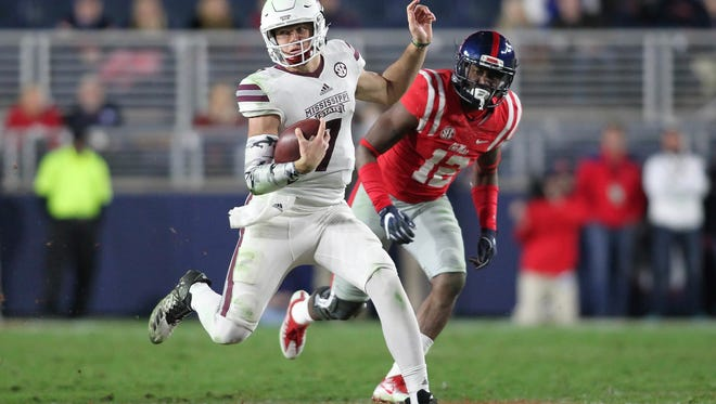 Mississippi State quarterback Nick Fitzgerald (7) runs downfield against Mississippi defender Tony Conner during their NCAA football game at Vaught-Hemingway Stadium in Oxford, Miss., Saturday, Nov. 26, 2016. Mississippi State won 55-20.