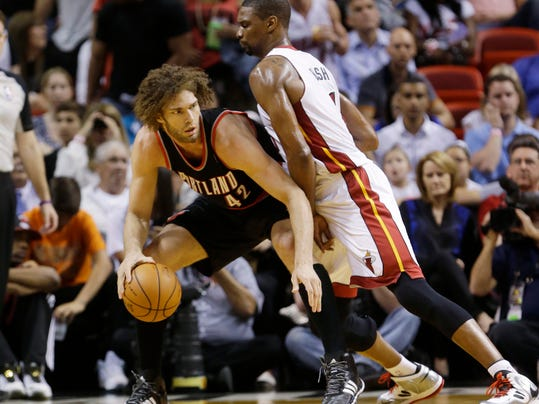Portland Trail Blazers center Robin Lopez (42) drives up against Miami Heat center Chris Bosh (1) during the first half of an NBA basketball game, Monday, March 24, 2014 in Miami. (AP Photo/Wilfredo Lee)