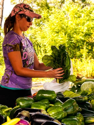 Kelly DeConinck of Spencerport bags up some produce for a customer.