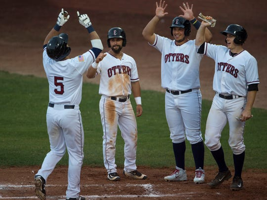 Evansville's Jeff Gardner (5) touches home plate as his teammates, from left, Josh Allen, Alejandra Segvia and Dane Phillips congratulate him on his grand slam against the River City Rascals at Bosse Field Wednesday evening. Gardner collected six rbi in the game.