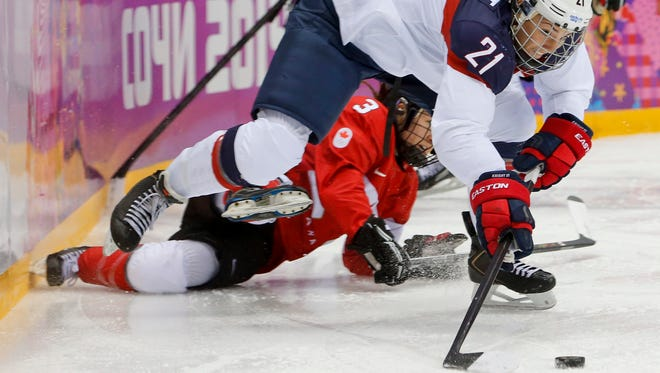 FILE - In this Feb. 20, 2014, file photo, United States' Hilary Knight passes the puck against Canada during the first period of the women's gold medal ice hockey game at the Winter Olympics in Sochi, Russia.