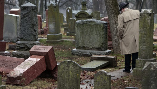 People walk through toppled graves at Chesed Shel Emeth Cemetery in University City, Mo., on Tuesday, Feb. 21, 2017. Authorities in Missouri are investigating after dozens of headstones were tipped over at the Jewish cemetery near St. Louis. (Robert Cohen /St. Louis Post-Dispatch via AP)
