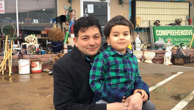 Gio Castro Hernandez stands with his son, Owen, in front of his shop, Gio's Treasures, in Waynesboro, Va., on Monday, Jan. 8, 2018, the day he found out his temporary protected status as an immigrant from El Salvador would be terminated.