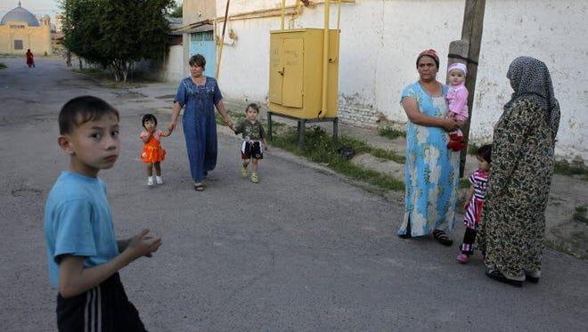 Uzbek women and children walk in the street of Tashkent, Uzbekistan, on May 22, 2010.