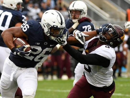 Penn State running back Saquon Barkley stiff arms Minnesota's