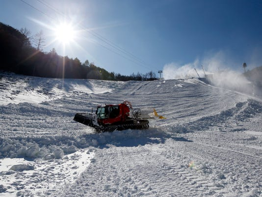 FILE - In this Wednesday, Jan. 13, 2016, file photo, a snowcat smooths the grade on the ski slope for the upcoming Pyeongchang 2018 Winter Olympics at the Jeongseon Alpine Center in Jeongseon, South Korea. With the Olympic Games coming to a close, one of the main questions facing South Korea and the consequences of hosting an expensive sports event is the future of the scenic Jeongseon Alpine Center, which was built in a formerly government-protected area where some 60,000 trees were razed.  (AP Photo/Lee Jin-man, File)