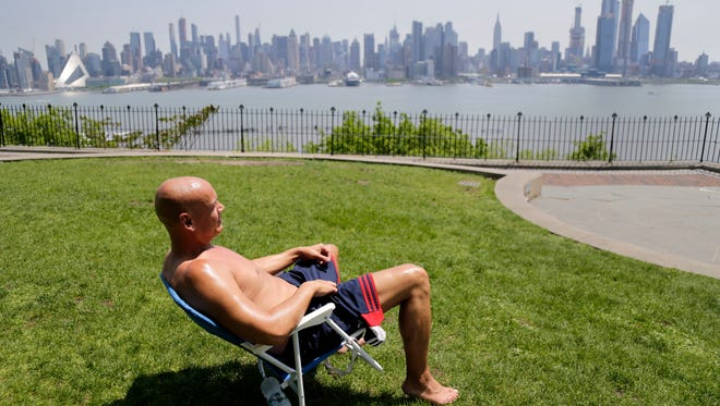 In this Tuesday, May 15, 2018 file photo, Rick Stewart sits in the sunshine with the New York City skyline in the background, in a park in Weehawken, N.J. According to weather records released on Wednesday, June 6, 2018, May was the warmest May on record across the USA.