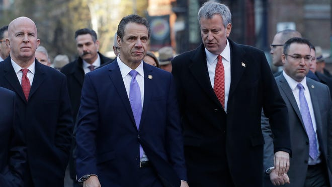 New York Gov. Andrew Cuomo, center, and Mayor Bill de Blasio arrive for a news conference, Monday, Dec. 11, 2017, outside the Port Authority Bus Terminal in New York. Police said a man with a pipe bomb strapped to his body set off the crude device in a passageway under 42nd Street between Seventh and Eighth Avenues. Police Commissioner James O'Neill is at left.