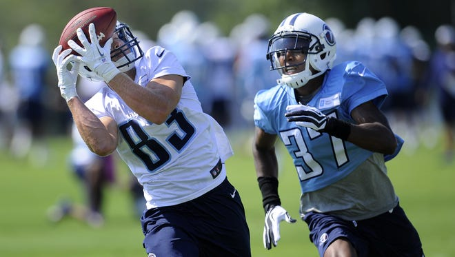 Titans wide receiver Marc Mariani pulls in a pass over defensive back Tommie Campbell during practice at Saint Thomas Sports Park on Saturday.