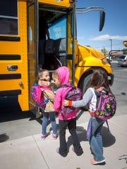 Central Elementary School students board a school bus