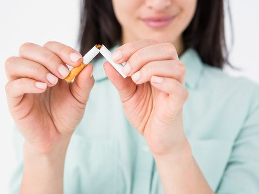 Smiling woman snapping cigarette in half