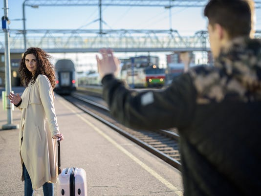 Separation of young couple woman leaving with suitcase at train station platform while boyfriend waving