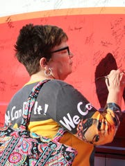 Peggy Dreyer, of Elmore, signs Rosie, the National Federation of Republican Women's campaign bus.