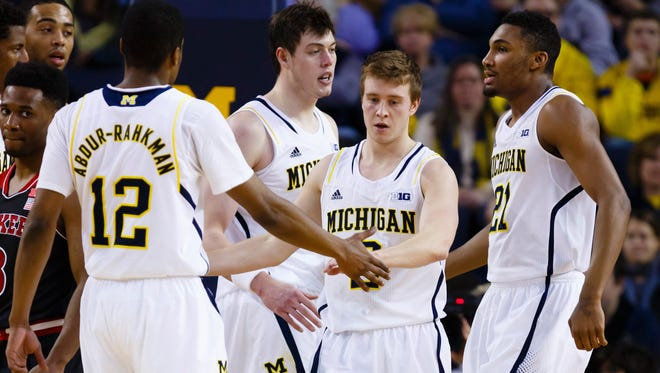 Michigan Wolverines guard Spike Albrecht receives congratulations from guard Muhammad-Ali Abdur-Rahkman and guard/forward Zak Irvin after making a basket and getting fouled in the second half against Nebraska at Crisler Center on Jan. 27. 2015.