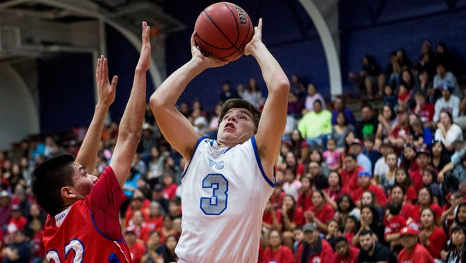 Valley Christian sophomore point guard Matthew Svorinic shoots over Holbrook junior guard Abrian Dickinson on Friday, Feb. 20, 2015 in Phoenix.