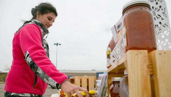 Anna Hintz of Sweet Bees in Cranmoor organizes her stand Thursday at the Farmers Market in Wisconsin Rapids.