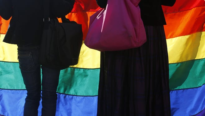 Members of the Montenegrin gay community hold a rainbow flag during a gay pride march in Podgorica, Montenegro, Sunday, Nov. 2, 2014.