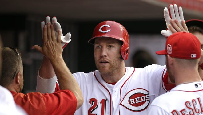 Cincinnati Reds third baseman Todd Frazier (21) is congratulated in the dugout after his solo home run.