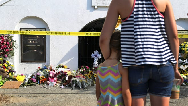 People mourn together in front of the Emanuel African Methodist Episcopal Church after a mass shooting at the church that killed nine people of June 19, 2015.