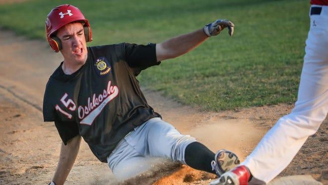 Matt Luft (15) of Oshkosh slides into third base during Friday's game against Neenah at E.J. Schneider Field.