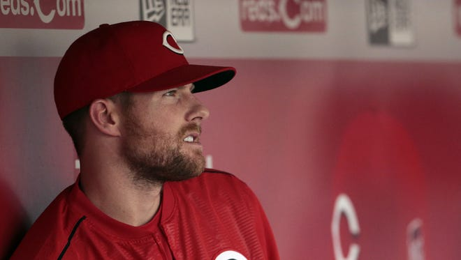Injured Reds shortstop Zack Cozart watches a game from the dugout.