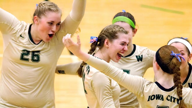 West High's Colby Greene (26), Ali Tauchen (10) and other teammates celebrate a point against City High on Tuesday.