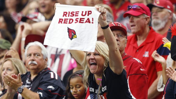 Arizona Cardinals fans cheer for their team as they